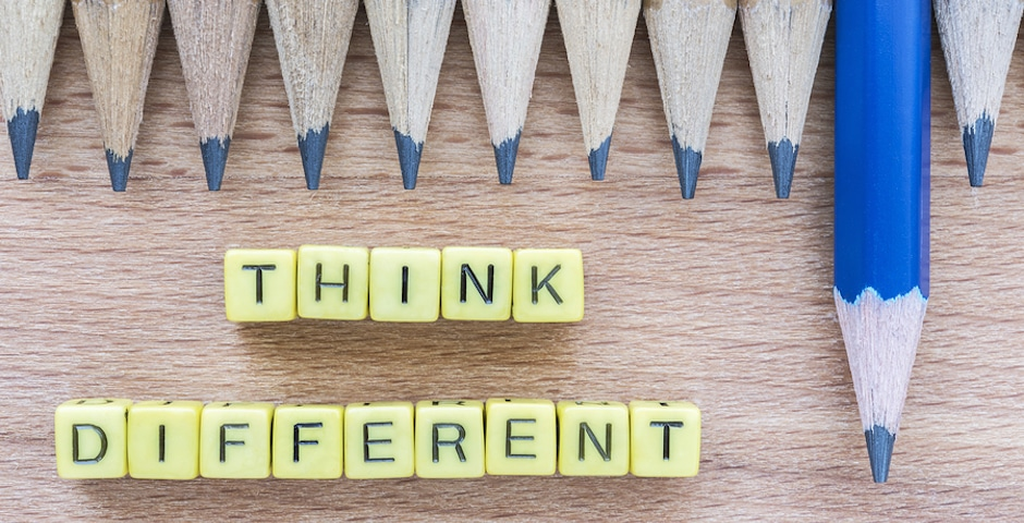 Words Think Different motivational slogan on wooden table with group of pencils. Top view. Think Different business unique and success concept